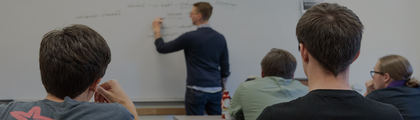 Discover academic success. Image of an instructor using a whiteboard in front of a class.